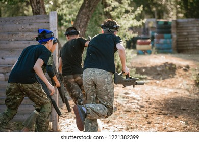 Group of men with guns playing lasertag game in forest