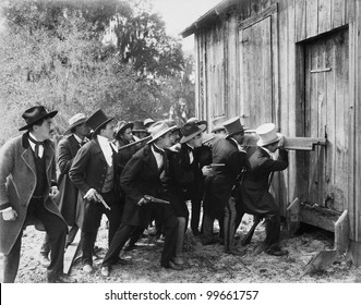 Group of men with guns and top hats breaking into a barn