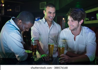 Group of men partying with glass of beer at bar counter in bar