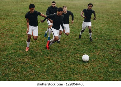 Group of men playing football on the field running for the ball. Soccer players running on field for possession of the ball.