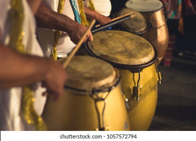 Group of men playing yellow drums at carnival parade at night. Brazil batucada musicians. Party event celebration concept. Loud music performers
