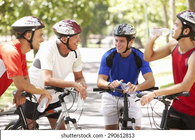 Group Of Men Resting During Cycle Ride Through Park