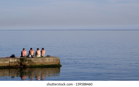 A group of men sit on a pier at the morning