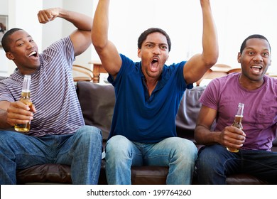 Group Of Men Sitting On Sofa Watching TV Together