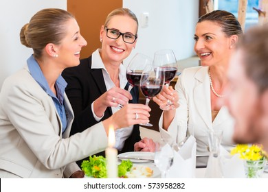 Group of men and women at business lunch in restaurant eating and drinking