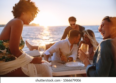 Group of men and women having a boat party during sunset. Happy young friends sitting at the back of a yacht and having fun.