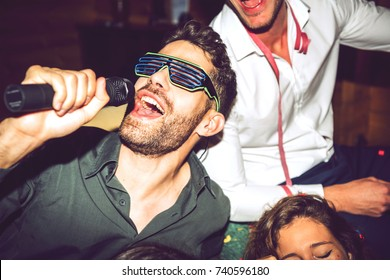 Group of men and women singing karaoke on glamorous party together.