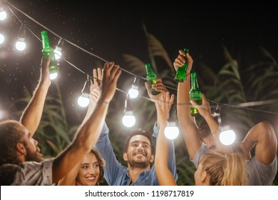 Group of men and women toasting with beer bottles at outdoor party.