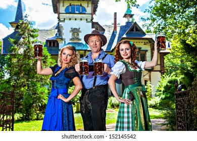 Group of men and women in traditional german Tracht with beer