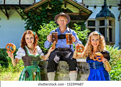 Group of men and women in traditional german Tracht with beer and pretzel