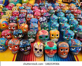 Group of Mexican handicrafts: ceramic skulls made and painted by hand in various colors with unfocused background, traditionally used to decorate the day of the dead.