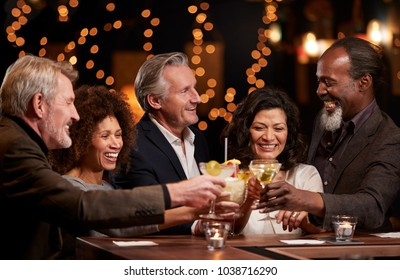 Group Of Middle Aged Friends Celebrating In Bar Together