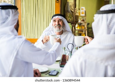 Group of middle eastern men wearing kandora bonding in a cafè restarant in Dubai