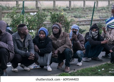 A group of migrants and refugees wait to leave the Jungle camp, Calais, France. November 2016.