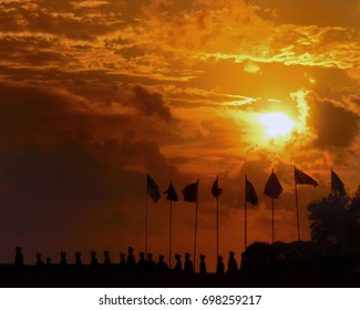 Group of Military Soldiers' Salutation in Sunset with Waving Flags. Silhouette