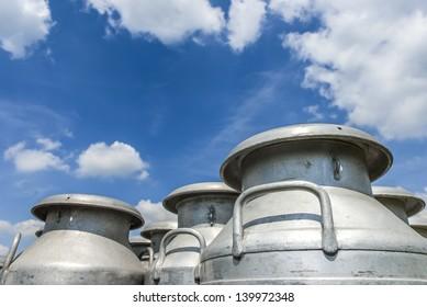 A group of milk churns against a blue cloudy sky.