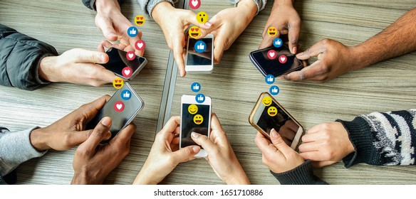 Group of millennial friends using mobile phones - Young people addiction to technology trends following and chatting with emoji on smartphones - Tech and millennial concept - Focus on bottom hands
