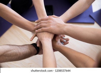 Group of millennial girls and guys stacked putting holding hands together before competition or during sport seminar, above top close up human palms. Like-minded people unity support teamwork concept