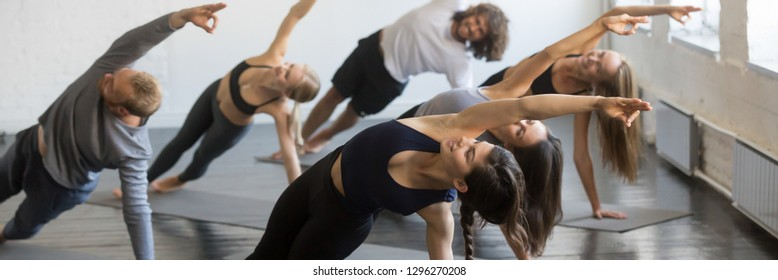 Group of millennial sporty girls and guys doing yoga Vasisthasana exercise, stretching in Side Plank pose. Active healthy wellbeing lifestyle concept. Horizontal photo banner for website header design