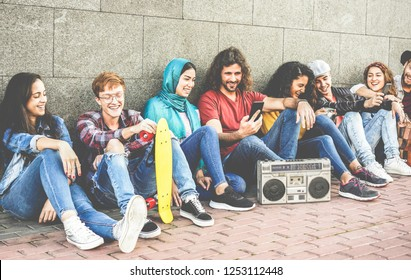 Group of millennials friends using smartphones and listening music outdoor - Young people having fun together with social trends - Youth, teen lifestyle and friendship concept - Focus on left faces