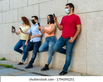 group of millennials girls and boys using their smarthphones during the corona virus outbreak period, use of prevention masks by young people, concept of new sociality and normality
