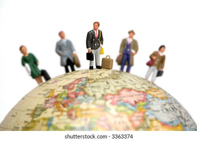 A group of miniature businessmen and businesswomen standing on a globe. Focus is on the man in the center with the others out of focus.