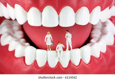 A group of miniature dentists and a dental assistant standing/sitting on human teeth.