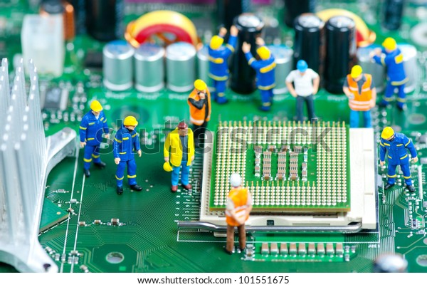 Group of miniature engineers inspecting computer processor
