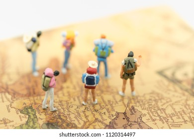 Group of miniature traveler with backpack stand and walking on vintage world map  using as background travelling or business concepts.