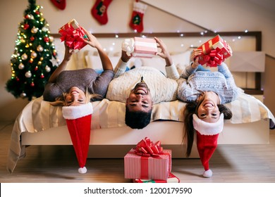 Group of mix raced friends celebrating christmas together. Lying on bed with christmas hats on their heads and looking at camera.