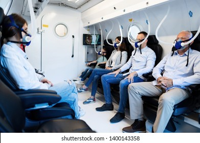Group of mixed age people wearing masks while having oxygen therapy in hyperbaric chamber.