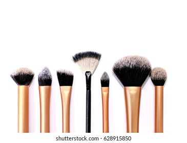 Group of mixed cosmetic brushes in random order, isolated on a white background