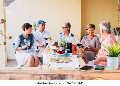 Group of mixed diversity ages sitting at the table having lunch together in friendship - family and friends concept with food and outdoor leisure activity, caucasian people eating  together