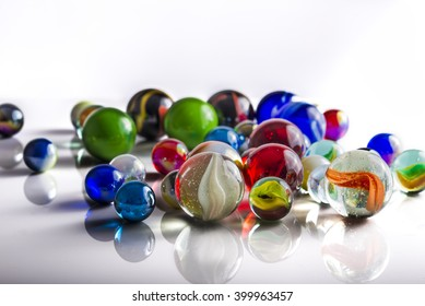 Group of mixed marbles on a reflective white surface