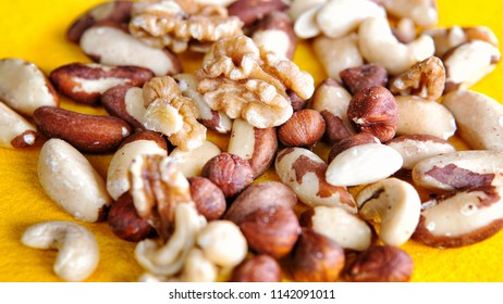group of mixed nuts on a yellow plate