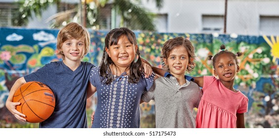 Group of mixed race children playing basketball in school courtyard.