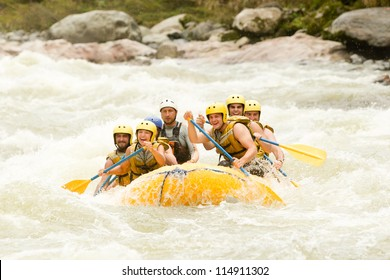 Group Of Mixed Tourist Man And Woman With Guided By Professional Pilot On Whitewater River Rafting In Ecuador