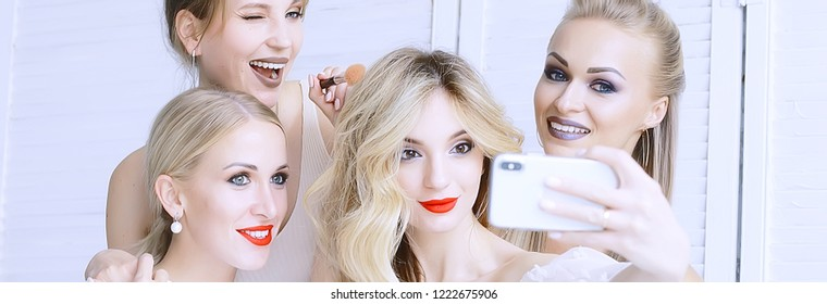 group of models make-up / four girls with professional make-up posing in the studio, a party of beautiful girls friends