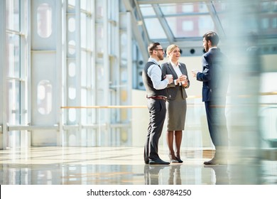 Group of modern business people chatting during coffee break  standing in sunlit glass hall of office building