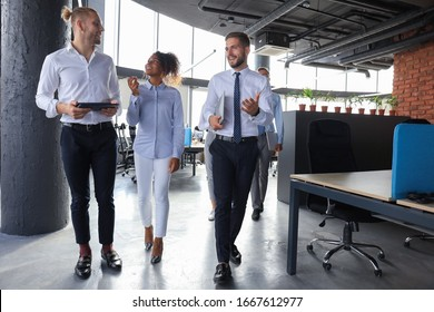 Group of modern business people are talking and smiling while standing in the office hallway