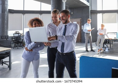 Group of modern business people are working using laptop and smiling while standing in the office hallway