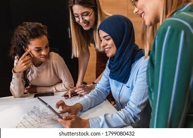 Gruppe von jungen, multikulturellen Geschäftsfrauen in Freizeitbekleidung diskutieren architektonische Entwürfe im Kreativbüro.