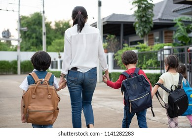 Group of mother and kids holding hands going to school with schoolbag. Mom bring children walk to school by bus together with satchel. Back to school and Education preschool. Parents son sister family