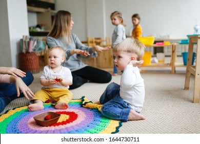 Group of mothers with babies in a lesson at a kindergarten center, Montessori kindergarten mom and baby, caucasian women with children