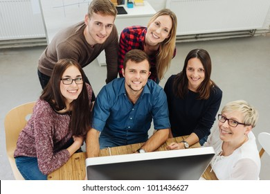 Group of motived happy young business people sitting grouped around a desktop monitor looking up to smile at the camera