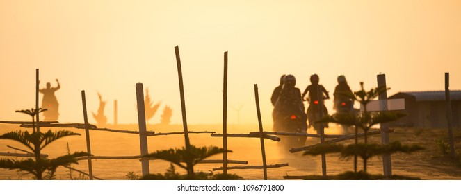 Group of motorbike with asian man and woman biker riding on dirt road in countryside of Thailand at sunset