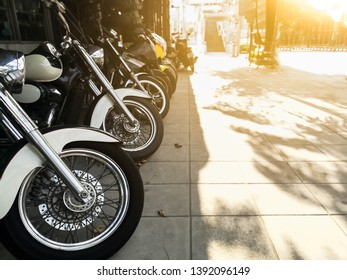Group of Motorcycle parked in a row on a street.