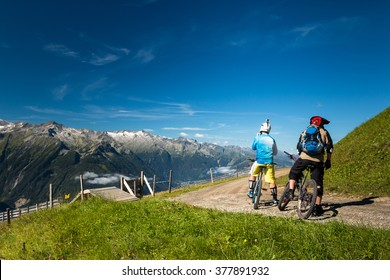 group of mountain bikers riding an enduro trail in the austrian alps in salzburg near kaprun with epic peak view