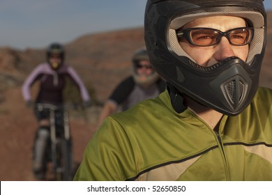 A group of mountain bikers is wearing protective eyewear and a helmets in a desert setting. Horizontal shot.