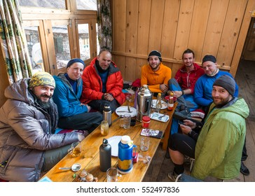 Group of Mountain Climbers men and woman having lunch together inside of wooden hut in Nepal Himalaya